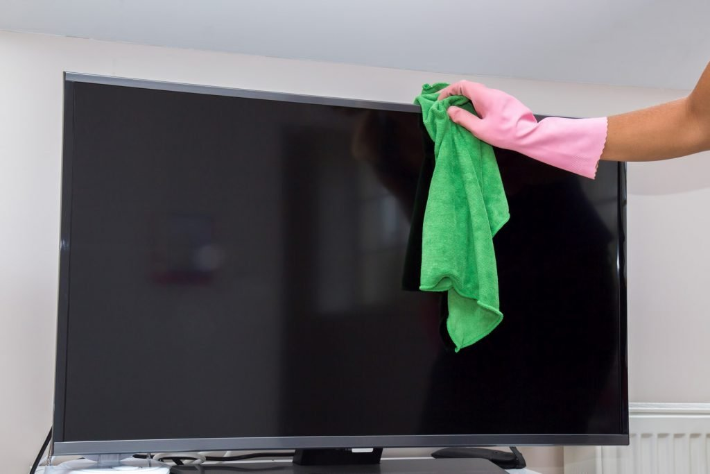Hand in protective glove carefully cleaning TV screen from dust